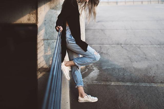 mladá dívka rotrhaných riflých