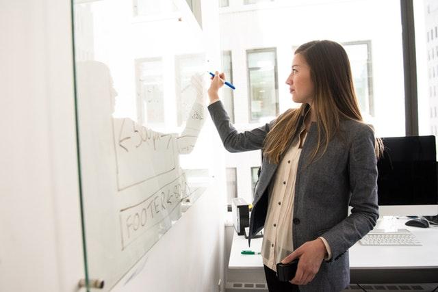 žena v kanceláři píše na tabuli, světlá halenka a šedé sáčko, dlouhé světlé vlasy