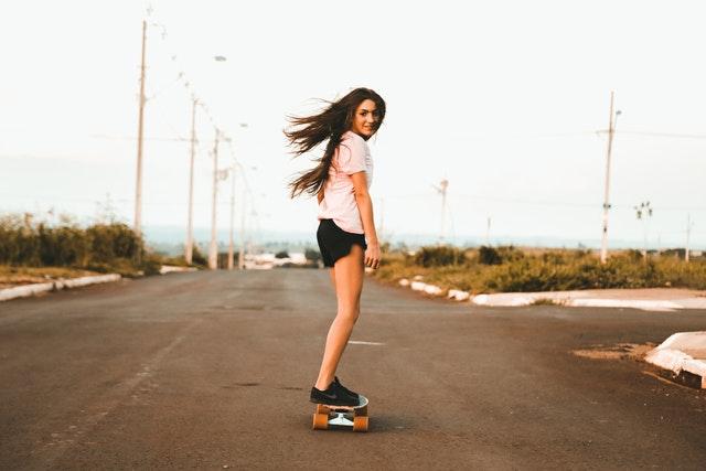 žena s dlouhými hnědými vlasy venku jede po ulici na skateboardu